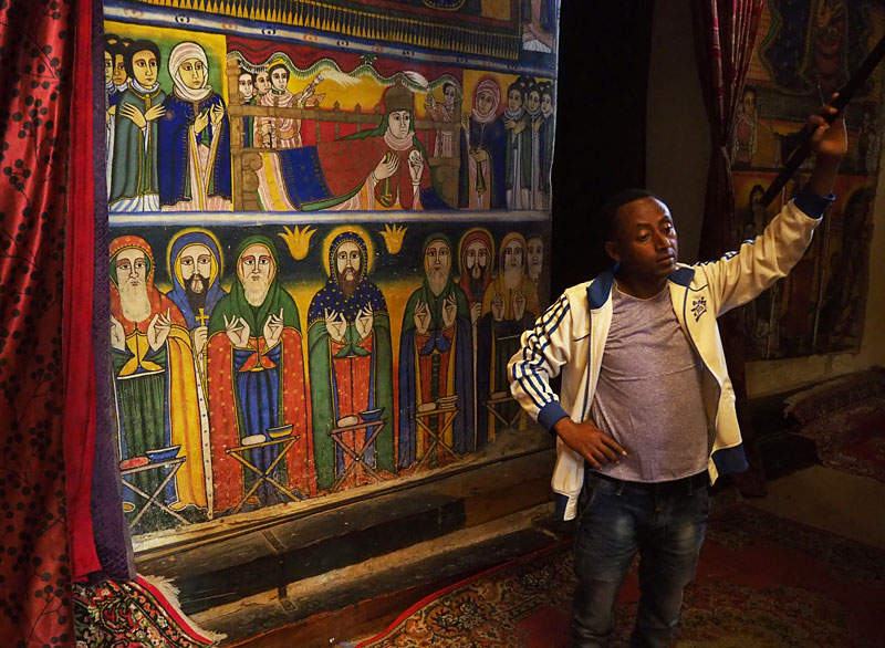 A guide lifts a curtain to reveal frescoes inside the 17th century Cathedral of St Mary of Zion in Axum, northern Ethiopia.