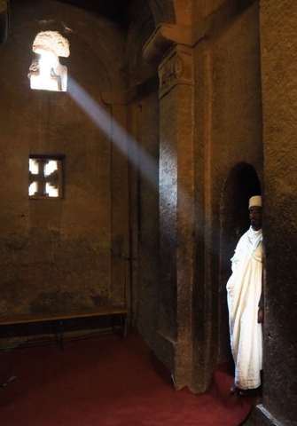 A ray of sunlight illuminates a priest in a rock-hewn church in Lalibela.