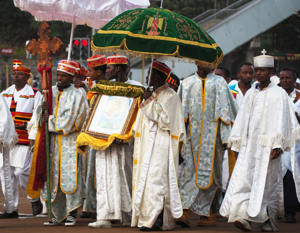 Priests protect a sacred icon with richly decorated parasols.