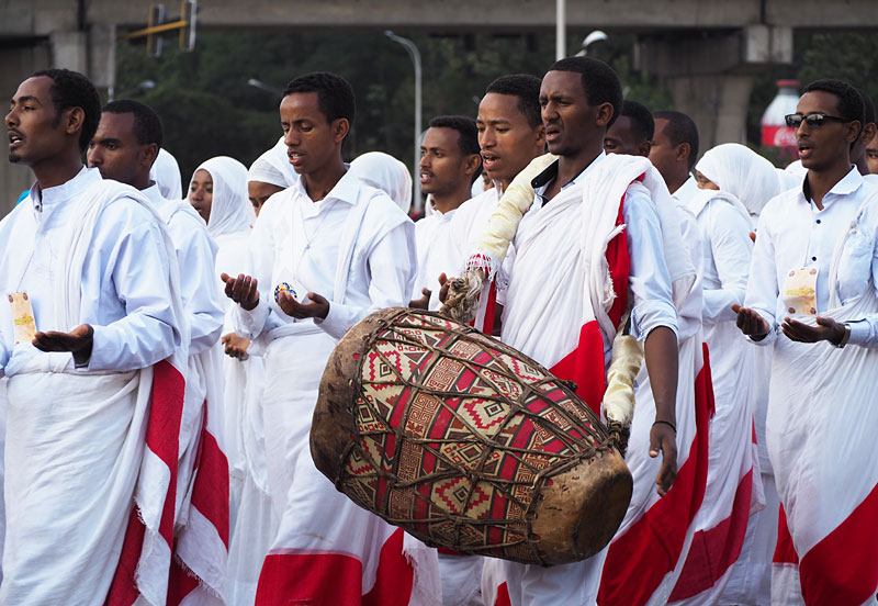A celebrant plays a traditional doubled-headed drum called a kebero.