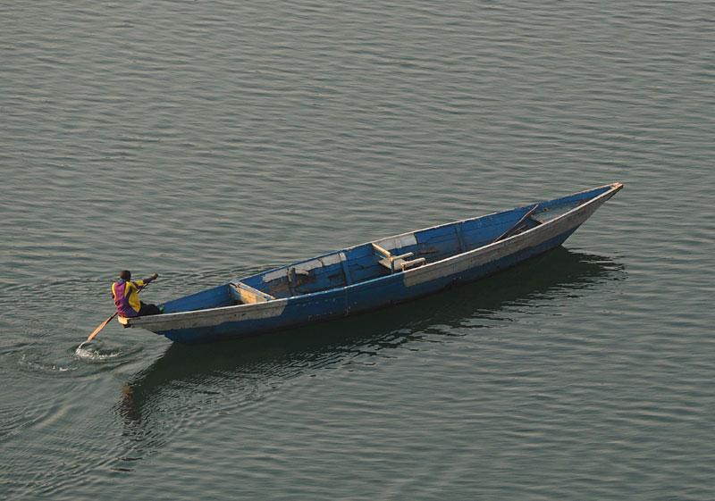 A man paddles a boat on Lake Kivu at dawn.