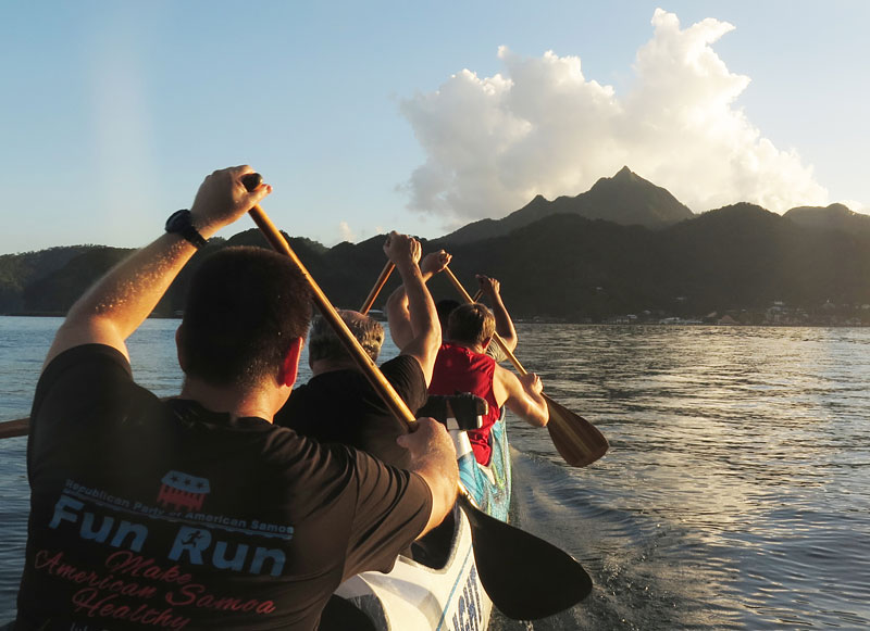 Members of Le Vasa Outrigger Canoe Club paddle in the shadow of Matafao Peak