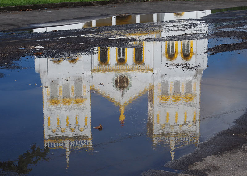 A church is reflected in a puddle in Leone village.