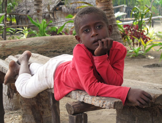 A child chills out on a bench in the Maskelyne Islands