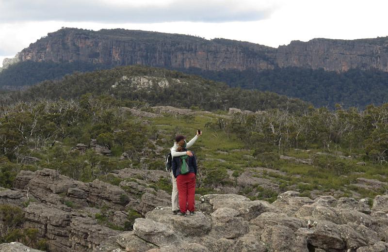 Bushwalkers pose for a selfie on the ridge above Halls Gap