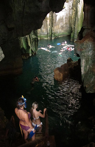 Swimmers descend the stairs into the first cave