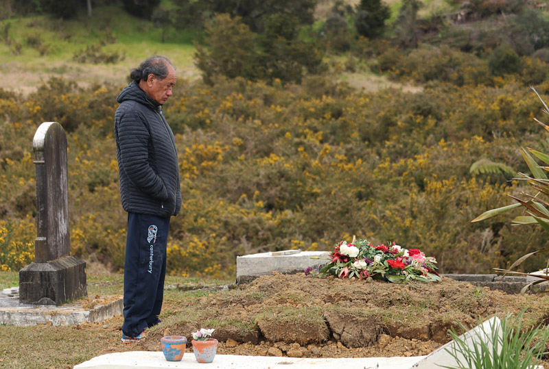 Paul Thomas at his brother's grave in Kaeo after a 40-year campaign to bring the SAS soldier's remains home
