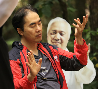 A tour group member practises qi gong next to a cut-out of Ilchi Lee