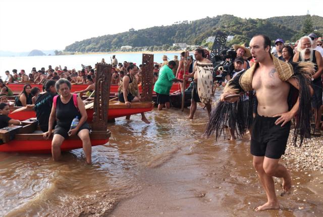 Rutene Gabel recites a chant as the waka land on Tii Beach