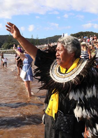 Kuia Ngaire Apiata recites a karanga (call) as the waka depart Tii Beach