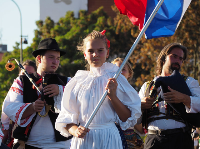 A young flagbearer leads a Slovak bagpipe band