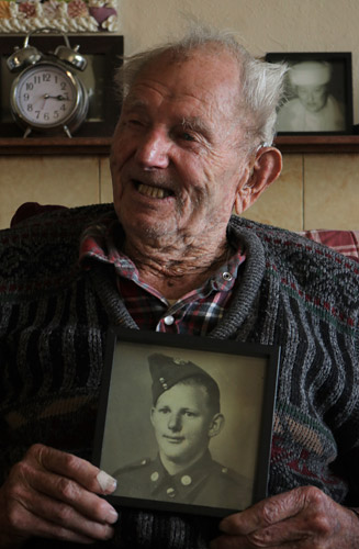 Bill Guest, 96, with a photo of himself as an 18-year-old
