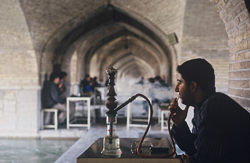 A man smokes a qalyan, or water-pipe, under the arches of the 17th century Si-o-seh bridge in Isfahan