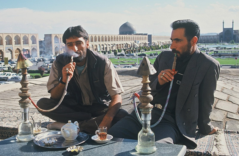 Men puff qalyan, or water-pipes, at a tea shop overlooking Isfahan's vast Imam Square