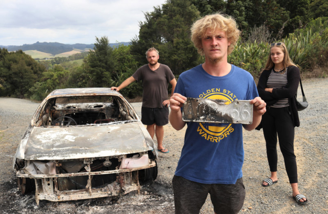 MARCH: German backpacker Marvin Rieger with all that was left of his car after it was stolen and torched at Paihia. Photo: Peter de Graaf