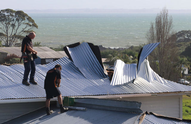 JUNE: Workers repair a roof damaged when a tornado hit Coopers Beach. Photo: Peter de Graaf
