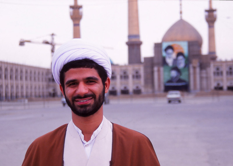 Friendly mullah Ali with Ayatollah Khomeini's mausoleum under construction behind him
