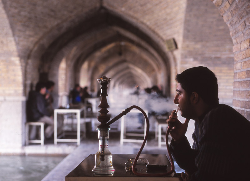 A man smokes a qalyan in a tea house under the arches of the 17th century Si-o-Seh Bridge in Esfahan