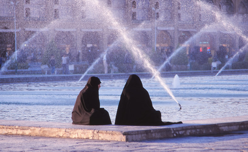Women in chador relax by a fountain on Esfahan's Iman Square