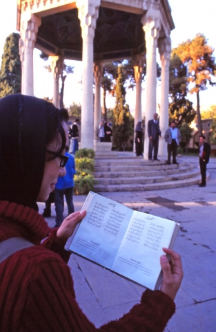 A girl reads poetry at the tomb of the 14th century Persian poet Hafez, in the city of Shiraz