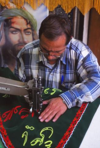 A man sews a religious banner in a Tehran bazaar