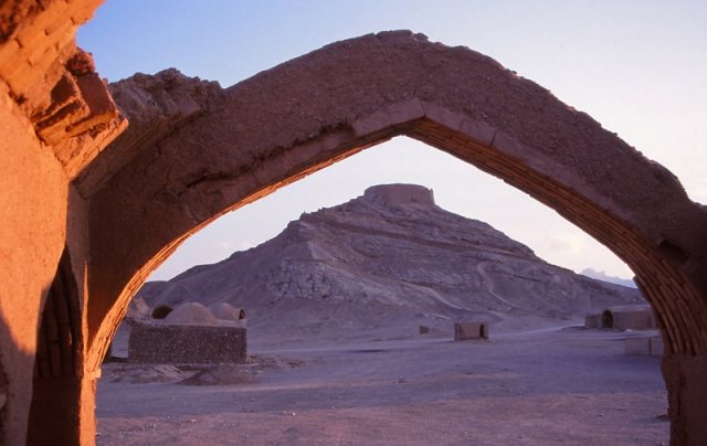 A Zoroastrian Tower of Silence is framed by a ruined arch in Yazd