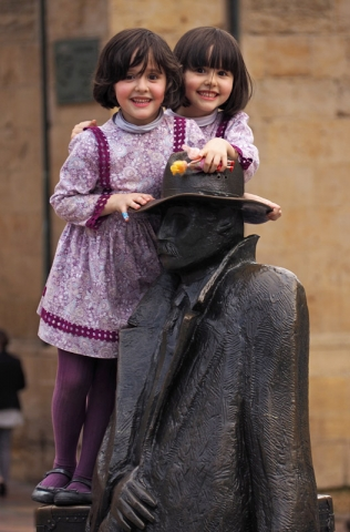 Twins play on a statue in Oviedo, northern Spain