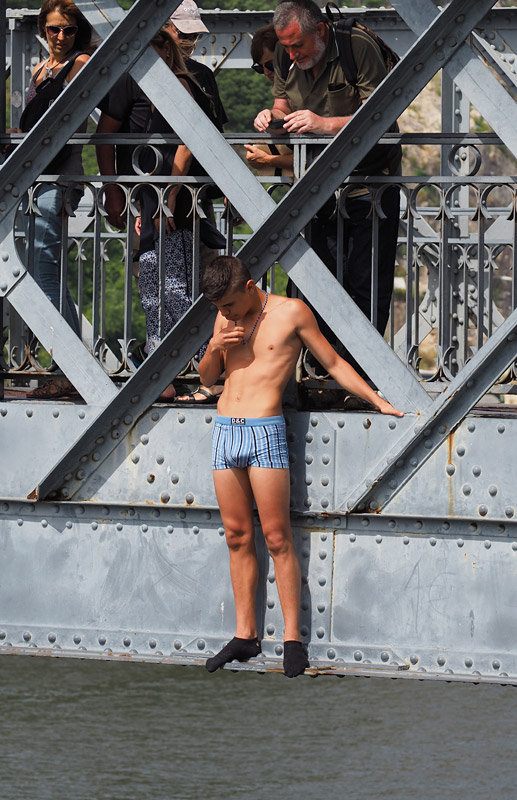 A boy clad only in socks ands boxers plucks up courage before jumping from a bridge in Porto