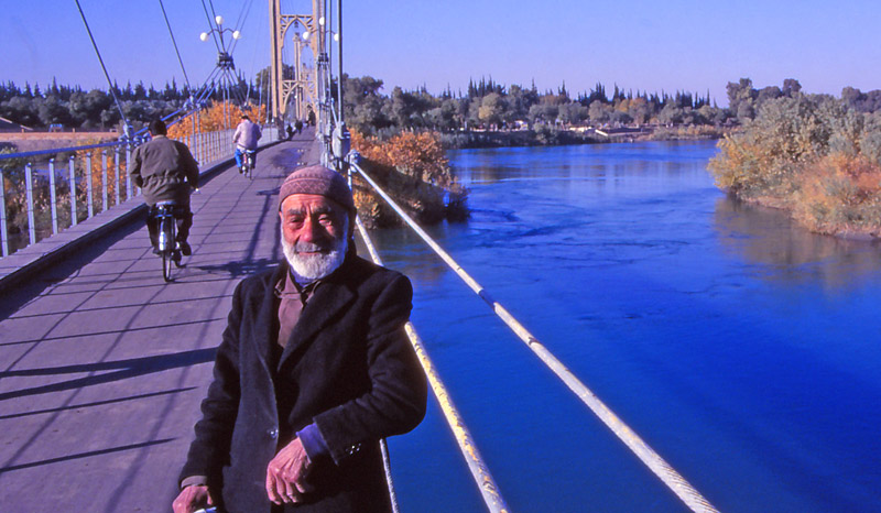 A haji (man who has been to Mecca) on a footbridge over the Euphrates River