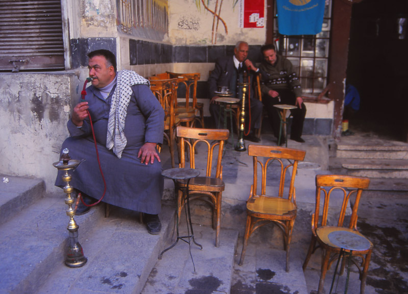 A customer smokes a nargileh (water pipe) in a Damascus cafe