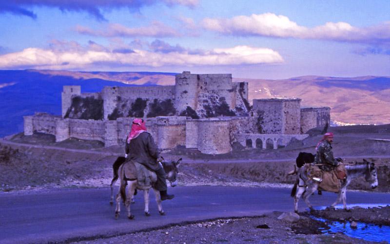 Men ride mules past the crusader castle Krak des Chevalliers in 1995