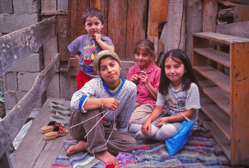 Girls knit by the roadside in the mountain village of Yusufeli