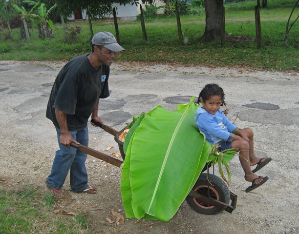 Sione Vailea takes his nephew for a ride in a wheelbarrow in Houma village, Tongatapu
