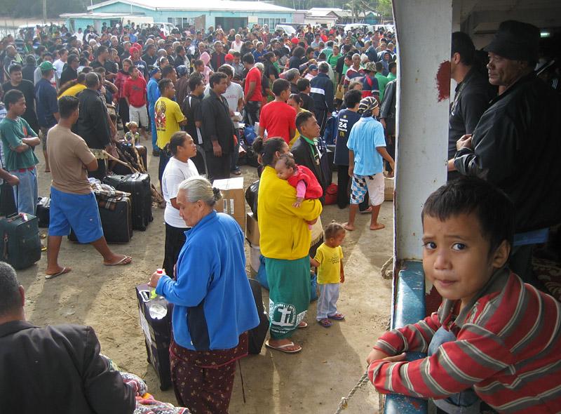 A boy watches as crowds board the ferry MV Pulupaki