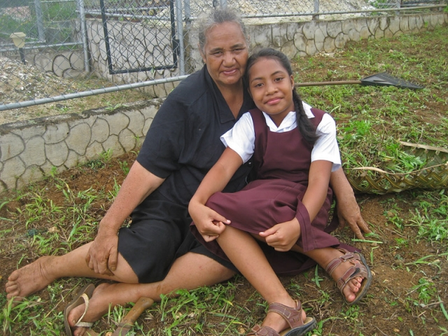 A girl and her grandmother rest after weeding a cemetery in Neiafu, Vava'u