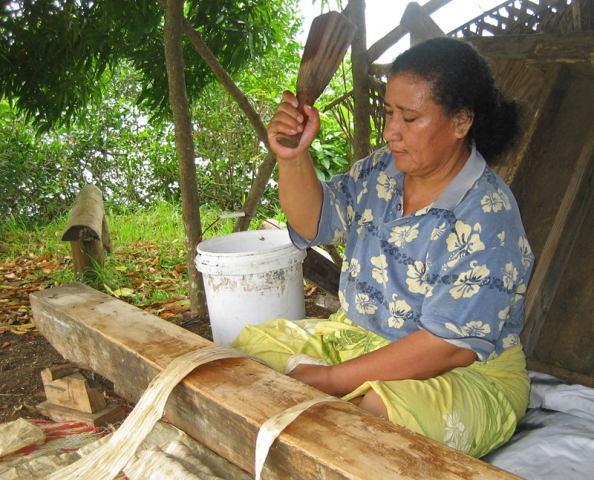 A woman beats paper mulberry bark into tapa cloth, Tongatapu Island