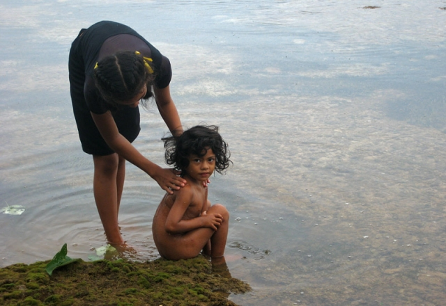 A girl washes her sister in a rock pool at Toula village, Vava'u