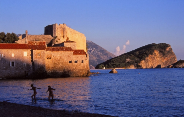 Montenegro, 1999: Swimmers emerge from the water next to the walled city of Budva