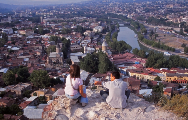 A couple admires the view over Tbilisi from Narikala Fortress