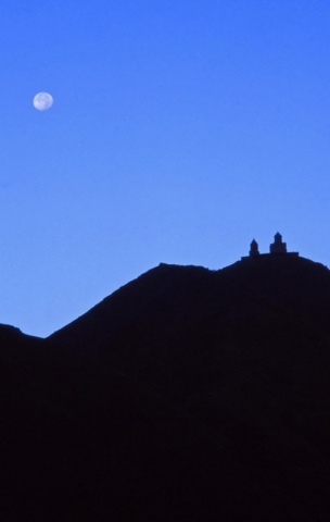 The moon rises behind the 14th century Tsminda Sameba Church near Kazbegi