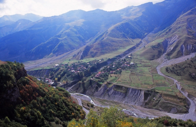 A village clings to the side of a valley in the Caucasus Mountains