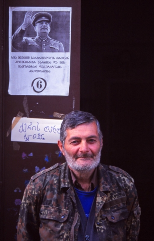 A passer-by insists on being in my photo of a Stalinist Party poster in Sighnaghi