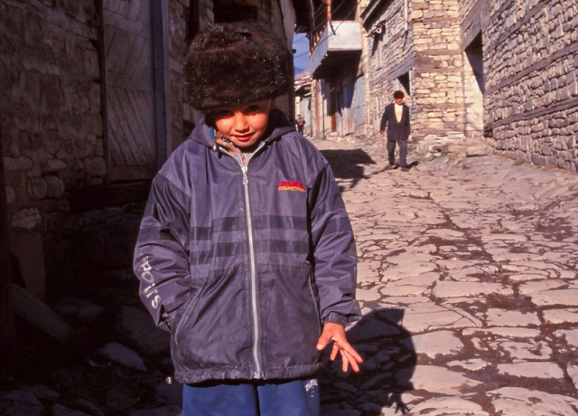 A boy keeps warm on the main street of Lahıc
