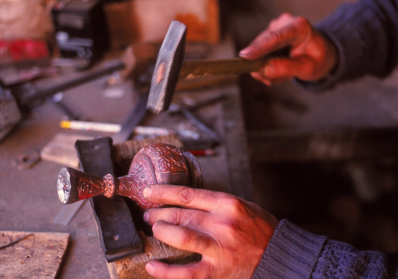 A craftsman works on a copper vase in Lahıc