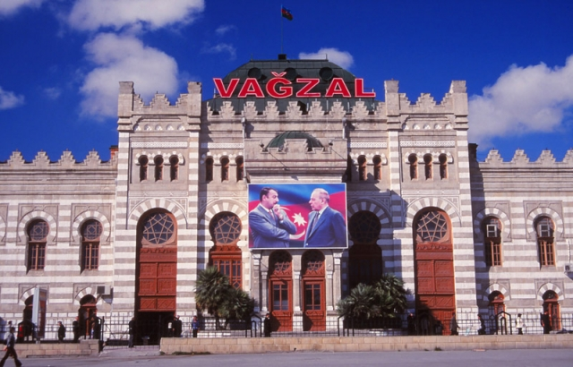 Baku railway station with a billboard of the president and his son