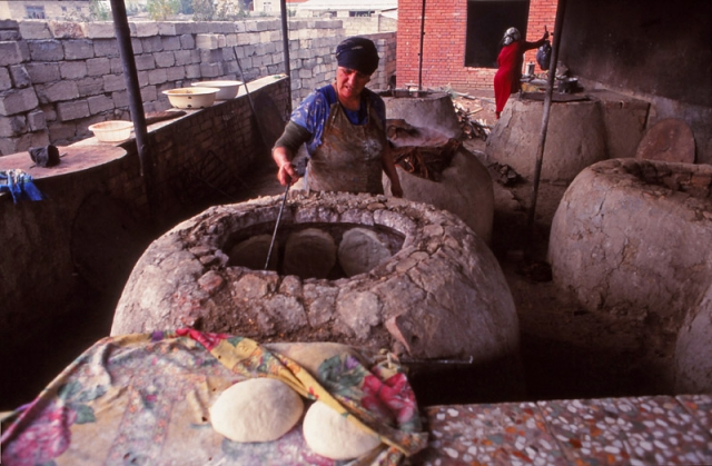Women bake bread by sticking the dough to the sides of wood-fired ovens