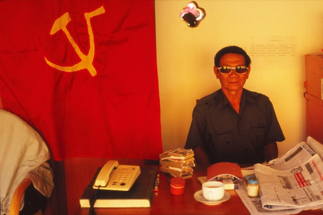 Official with communist flag at Pha That Luang, Vientiane