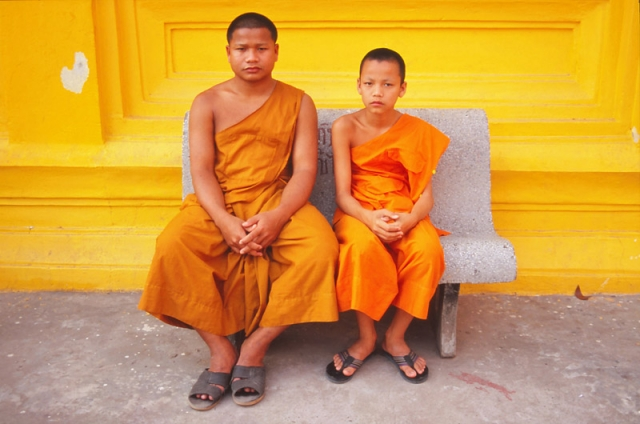 Monks share a bench at a monastery in Vientiane