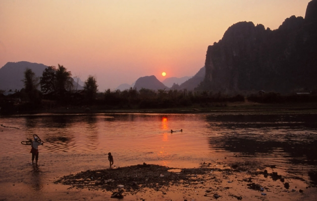 A cyclist looks for a good spot to cross the Nam Xong River, Vang Vieng