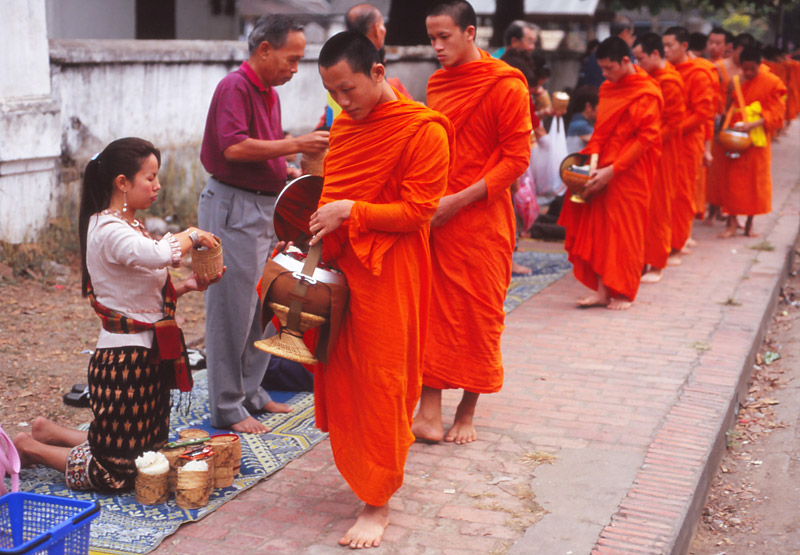 Devout Buddhists offer monks alms of sticky rice at dawn in Luang Prabang